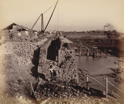 Wall of north jetty showing portion of tunnel in wall arched over. Excavation of bay nearly completed [Victoria Dock construction, Bombay].